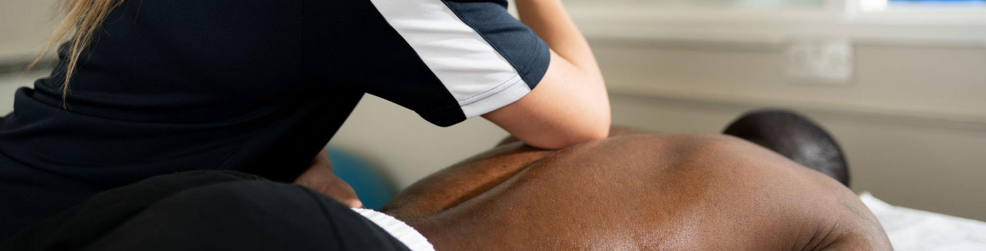 A staff member massaging a mans back