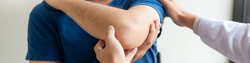A physiotherapist is holding and examining Tennis Elbow